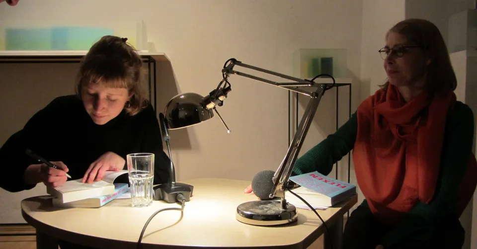 Autorin und Herausgeberin Mia Göhring beim signieren, rechts Moderatorin Beate Weinkauf